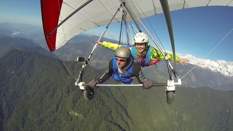 The girl waves her hands in tandem flight on a hang glider