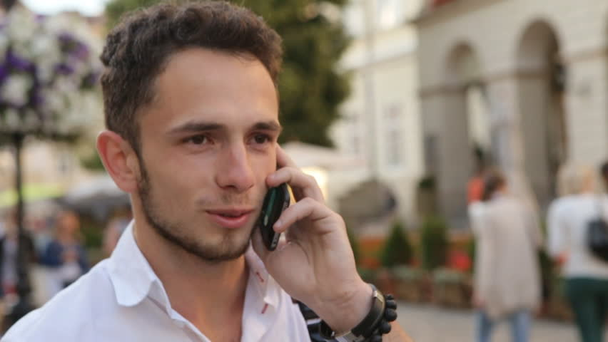 Smiling man in his 20s talking of cellphone outdoors. Handsome guy speaking on phone and doing beautiful smile. | Shutterstock HD Video #14238095