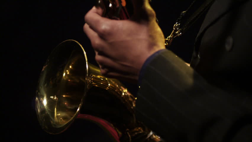 Jazz musicians play their instruments against a black background with colorful splashes of lights. Instruments include a Saxophone, Cello, Violin, Trumpet, and a Soprano Sax.