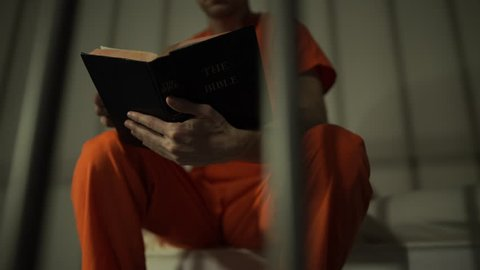 Scene of an inmate reading a bible in prison