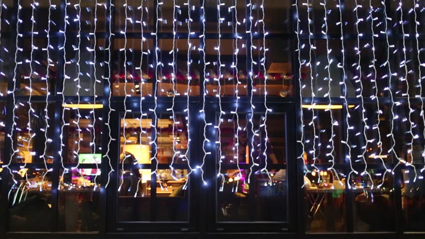Big window with electric garland in reflection which tables and waiter outdoor