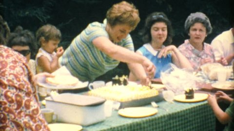 AKRON, OHIO, JULY 15, 1967: A mom cuts delicious birthday cake for her family at the big summer reunion in 1967.