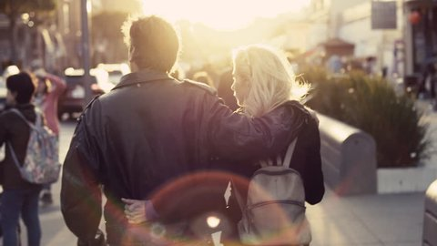 Middle-aged couple walk down the street during sunset as they explore the local market.
