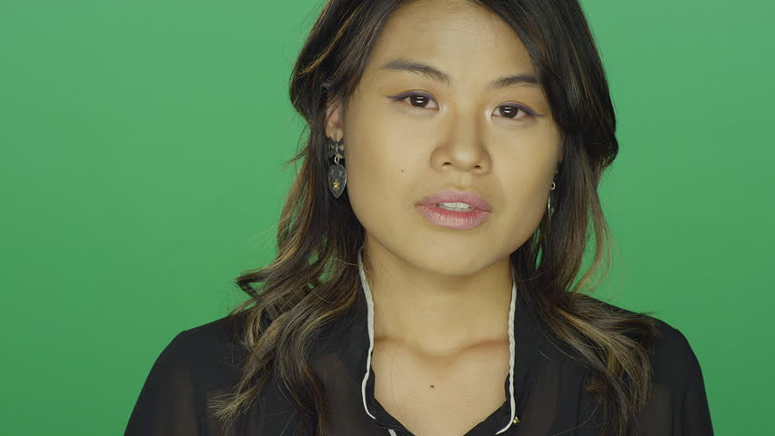 Young asian woman looking sad, on a green screen studio background | Shutterstock HD Video #14360212
