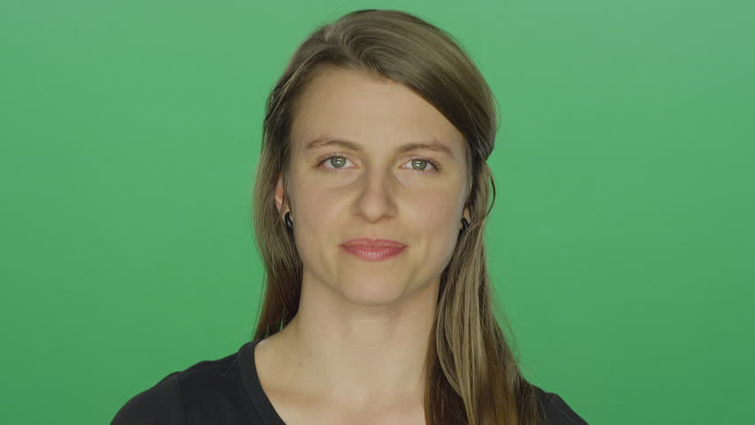 Young woman smiles, on a green screen studio background | Shutterstock HD Video #14361322
