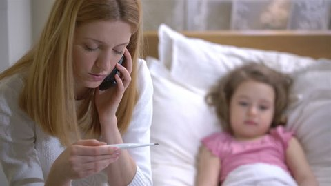 Mom is measure the temperature of little girl and call the doctor. 4K.