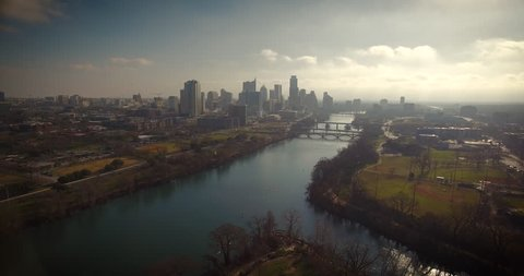 Downtown Austin, Texas is featured in this beautiful early morning shot as the camera starts at a high altitude and then lowers while the camera pans up, keeping the city in focus.