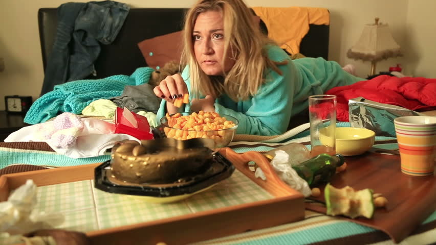 Portrait of a lonely sad, miserable woman with bad looking lying on a bed eating unhealthy foods and watching tv
