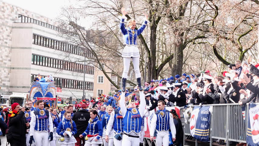 Cologne, Germany - February 8, 2016. Traditional street carnival. Unidentified people cheering carnival floats and traditional groups at the street parade. Carnival is a yearly festival.