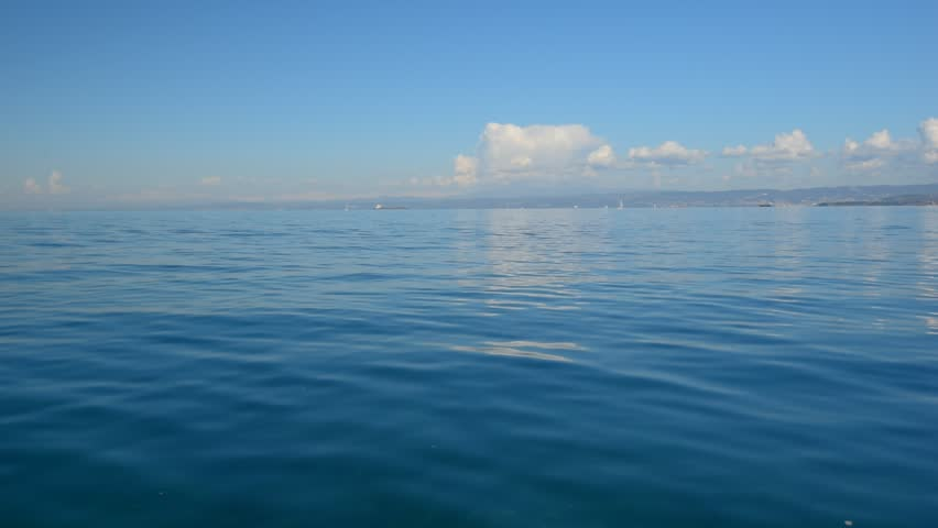 Sea view, seascape, nature background: sea surface, blue sky, clouds, clean water, ripple, clouds reflection in the water on the background. Universal nature, resort, summer vacation background.