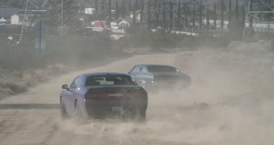 SLOW MOTION cars in desert car chase speed along dirt road away from camera, kicking up dust, as helicopter pursues above #14496832