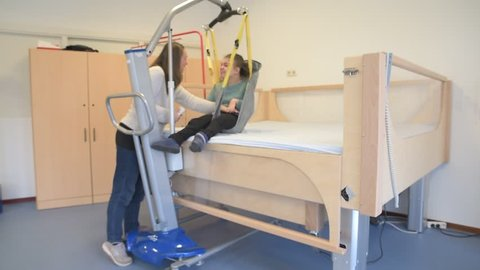 A disabled child being cared for by a special needs carer using specialist equipment / Working together with disability
