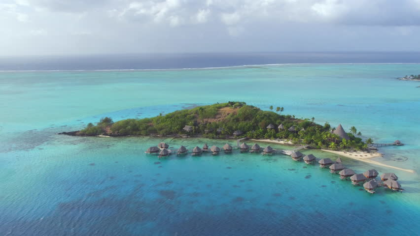 AERIAL: Luxury oceanfront hotel resort on secluded tropical white sandy beach, infinity swimming pool and deluxe overwater villas secluded accommodation on exotic island Bora Bora in French Polynesia