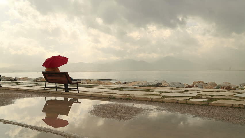 Woman with umbrella sitting alone on the seaside bench and be lonely, rainly day