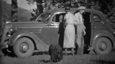 DENVER, COLORADO 1935: Couple loading black dog into car in mountainous forest.