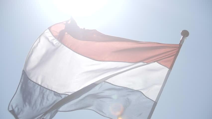 Dutch flag against blue sky with lens flare.