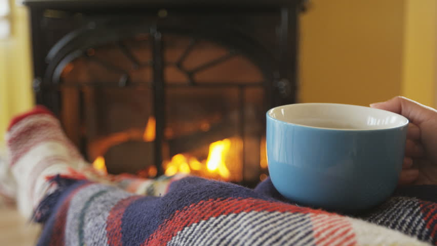 Woman drinking coffee cup nearby fireplace. Girl is covering herself with blanket while having hot drinking getting warm in her living room. She is warming herself in front of burning stove in winter.