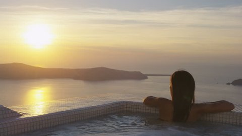 Asian woman relaxing at the edge of swimming pool at resort. Young female is watching beautiful view of sunset. She is enjoying her vacation at resort by sea. Santorini, Greece.