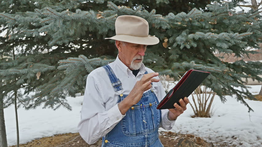 Old man in coveralls and a floppy cowboy hat with a grey goatee frustrated and struggling with computer tablet technology - outdoors with snow on the ground and a large pine tree in the back ground