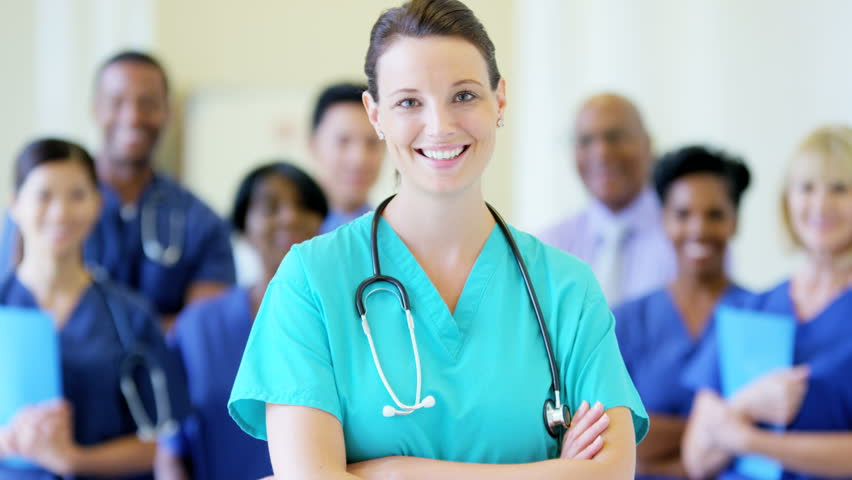 Portrait of confident Caucasian young female nurse and team of staff in hospital