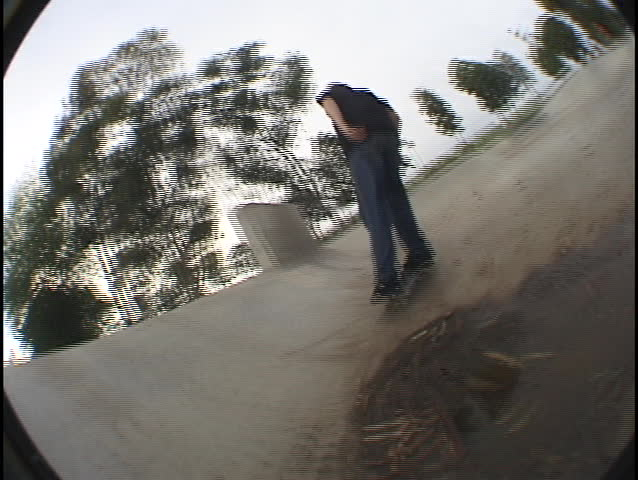 A skateboarder travels the edges and walls of a skate park.