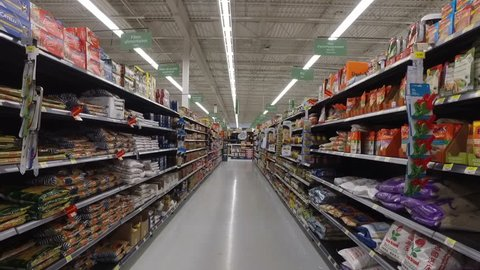 MONTREAL, CANADA - FEBRUARY 2016: Slow Motion: Walking through Walmart aisle (BBQ ingredients, ketchup, mayo, oils, food cans, sauces etc.)