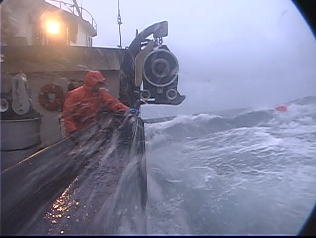 A lobster fishermen throws a rope out and catches a buoy in treacherous conditions while ocean fishing.