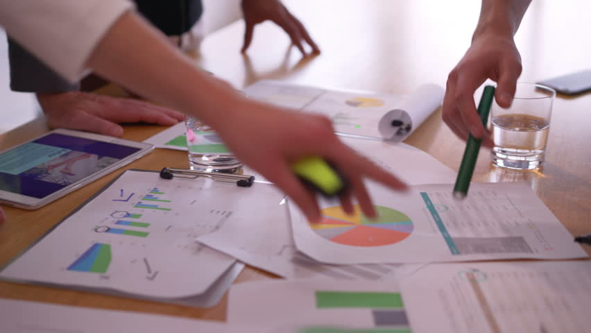 Unrecognizable young corporate startup team having a progress meeting looking at printed data and analyzing graphs. | Shutterstock HD Video #14698687