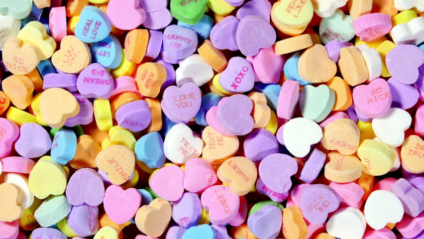 A Rotating Bowl Of Sweet Valentines Heart Shaped Candy In Various Pastel  Colors And Messages Of