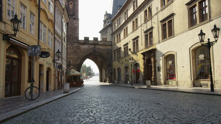 A moving shot along an empty street in Mala Strana looking east through the tower on the entrance to Charles Bridge.  A few runners can be seen in the distance. 4k.
