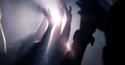 Slow mortion shot of young festive people with their hands raised and in the air at concert or party. Smoke is lingering in the nightclub and silhouettes of teenagers dancing.