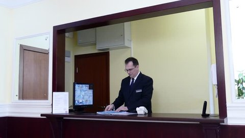 Apartment Concierge: Man on front desk with documents