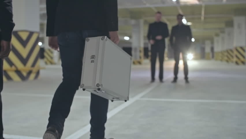 Two criminals walking towards their partners and opening metal briefcase in front of them
