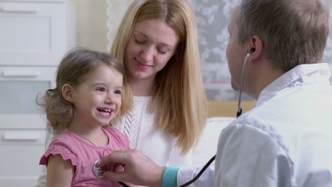 Male pediatrician examines baby with a stethoscope.