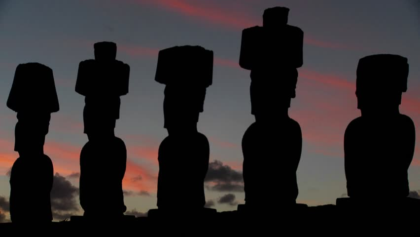 The sun sets behind Easter Island statues.