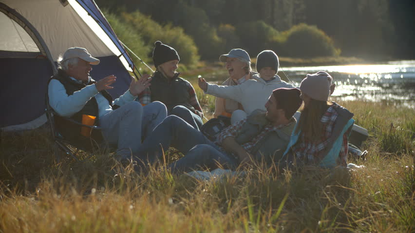 Multi generation family relaxing outside tent in countryside