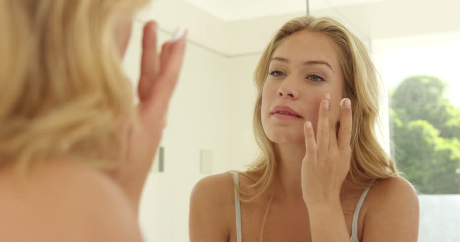 Young woman applying cream on her face in the bathroom