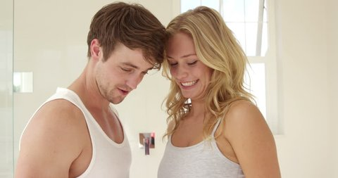 Happy Caucasian couple discover the pregnancy test in the restroom
