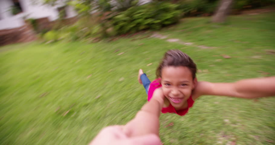 Point of view shot of father spinning his daughter by hands around in park. The girl laughing and having fun in Slow Motion