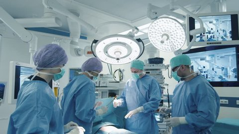 Medical Team Performing Surgical Operation in Bright Modern Operating Room. Shot on RED Cinema Camera.
