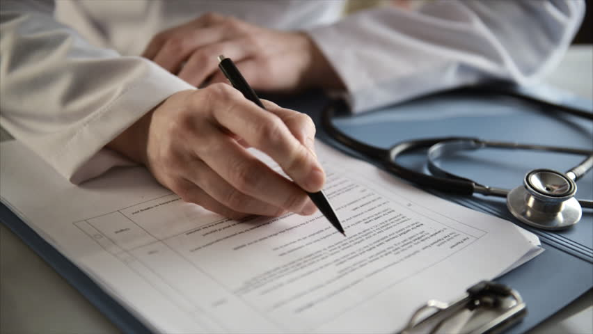 Female doctor doing paperwork in the office. Young therapist filling medical checklist sitting at the desk. Health care and insurance concept.