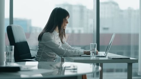 young business woman working at a laptop in modern office. she smiling and take a break