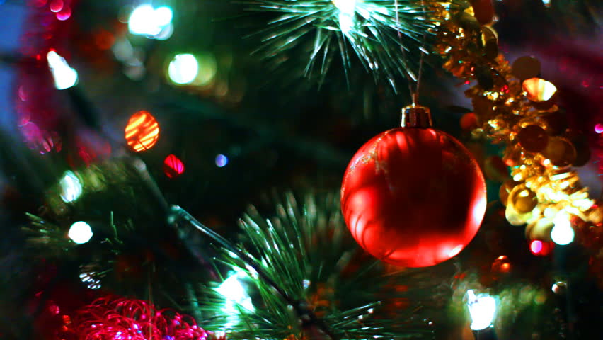 Glass Toy Red Ball Reflects Light Rays On Christmas Tree Among Of Blinking  Colored Garlands,