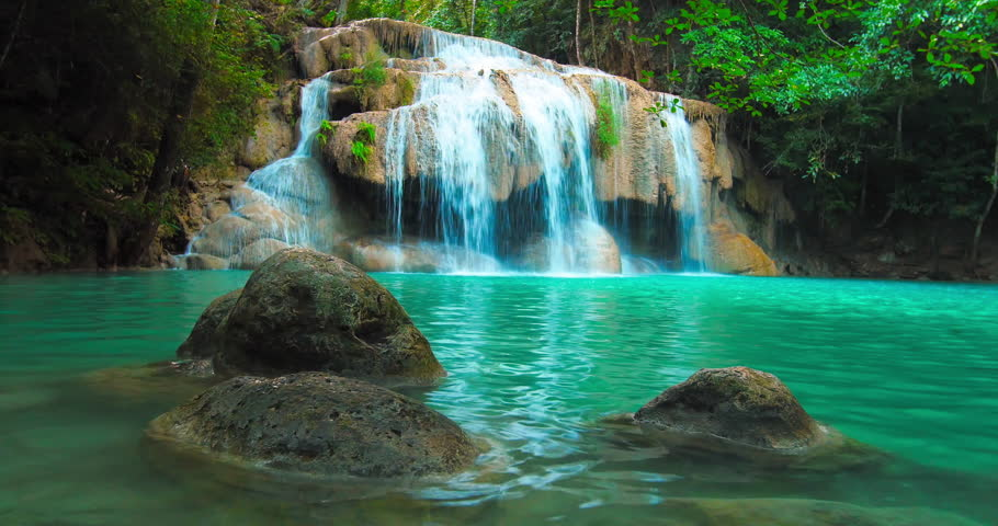 Beautiful waterfall cascade and natural pond with blue water in jungle forest