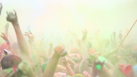 Celebration of Holi colors festival. Crowd waving hands at concert, open air festival,