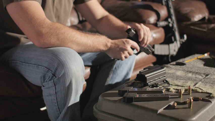 Slow motion shot of a man sitting alone in a room; he is disassembling and cleaning a .45 caliber semi-automatic handgun.