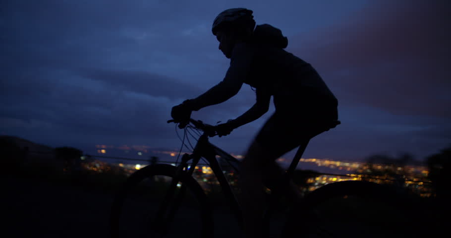 Upward shot of determined cyclist in recreational pursuit for competitive sport with bicycle on mountain side road just after sundown with mountain silhouettes in the background