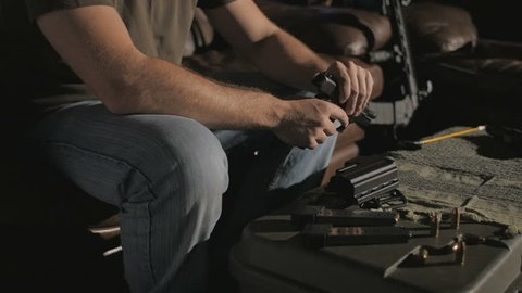 Shot of a man sitting on a couch. He takes the clip out of a .45 caliber handgun, disassembles the gun, then begins cleaning it.
