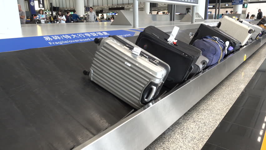 airport conveyor belt. hong kong - 19 october 2015: luggage has arrived on the conveyor belt at airport