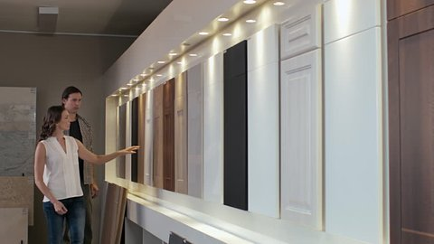 Couple browsing samples of cabinets cupboards in modern kitchen showroom home remodeling, renovation and makeover concept